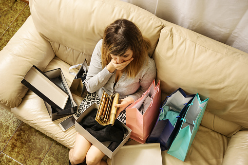 shopping addicted young woman left with no money looks worried for cashless wallet