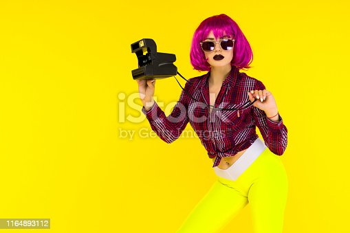 Fashion girl portrait with camera on yellow background. Crazy style young woman in pink wig - image