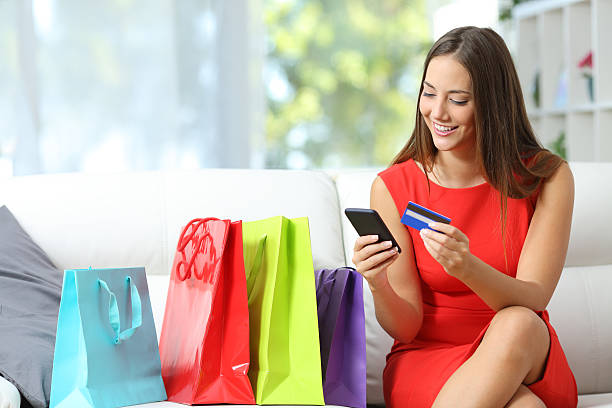 mode mädchen online-shopping mit taschen am - sofa online kaufen stock-fotos und bilder