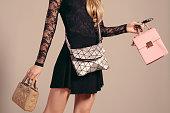 ファッションの女の子。若い女性の黒ドレスと 3 つの手のバッグでポーズ