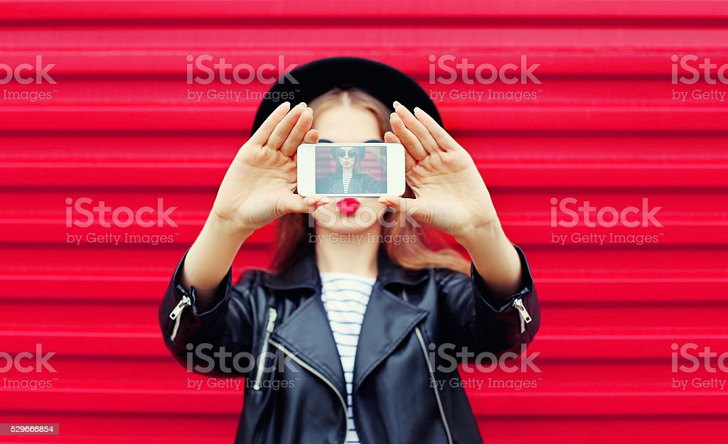 Fashion glamour woman makes self portrait on smartphone blowing lips stock photo