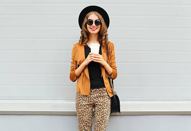 fashion happy smiling woman, coffee cup, wearing hat, jacket, handbag - bedruckte leggings stock-fotos und bilder