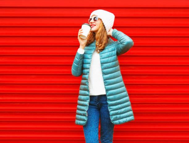 mode glücklich lächelnde frau trinkt kaffee auf rotem grund in der stadt - gute winterjacken stock-fotos und bilder