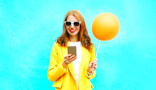 istock Fashion happy smiling woman using smartphone holds an air balloon on colorful blue background 1030600014