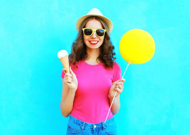 mode glücklich lächelnde frau mit gelben luftballon und eiskegel tragen strohhut und rosa t-shirt über bunten blauen hintergrund - eis ballons stock-fotos und bilder