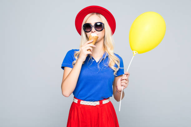 mode glücklich lächelnde frau mit gelben luftballon und eis kegel tragen stroh hut und farbe kleid über grauen hintergrund - eis ballons stock-fotos und bilder