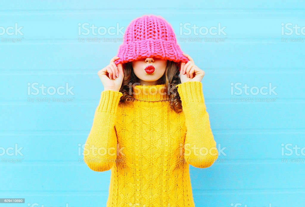 Fashion happy woman blowing red lips wearing knitted hat stock photo
