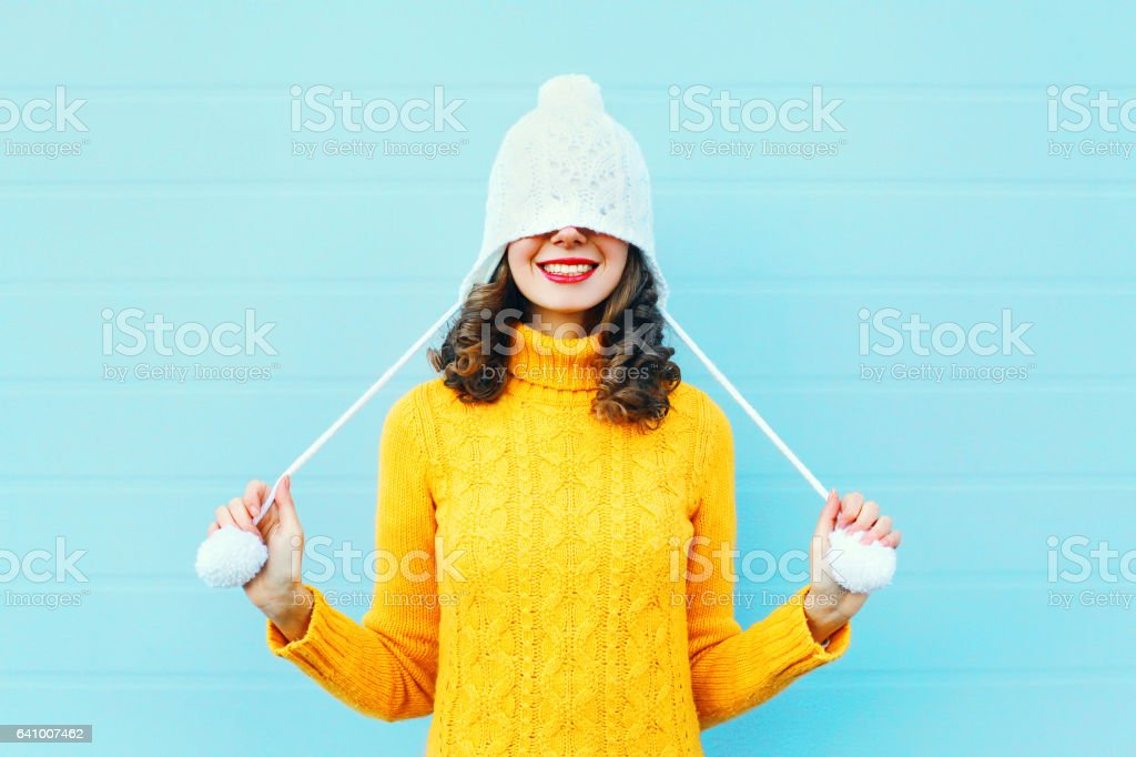 Fashion happy young woman in knitted hat and sweater having fun over colorful blue background stock photo