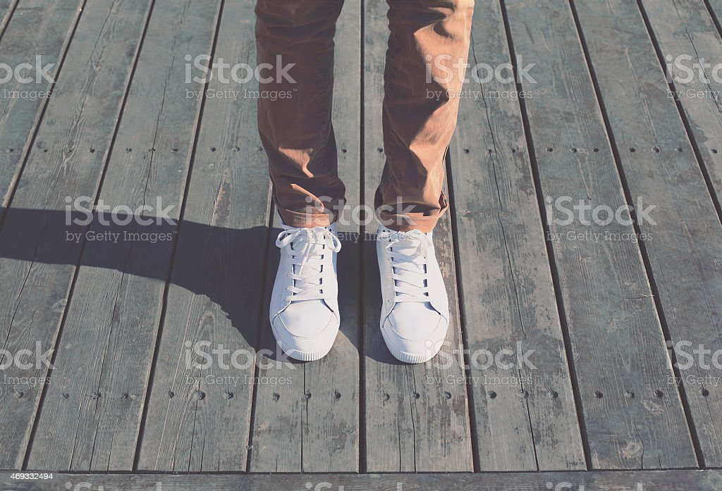 Fashion hipster cool man with white sneakers, soft vintage toned stock photo