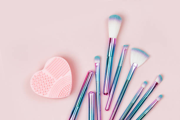 Fashion holographic colored makeup brushes with Brush Cleansing Pad on a pastel pink background. Flat lay, top view Fashion holographic colored makeup brushes with Brush Cleansing Pad on a pastel pink background. Flat lay, top view make up brush stock pictures, royalty-free photos & images