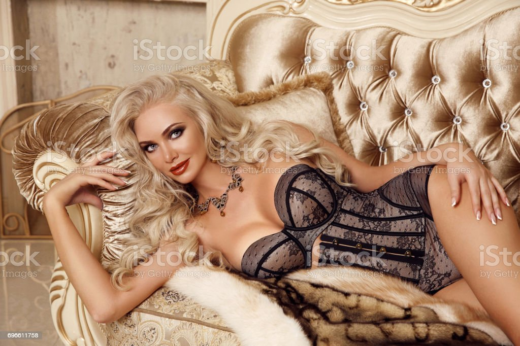 4bcc844ec Fashion interior photo of gorgeous sexy blond girl in lingerie corset lying  on luxury modern sofa in golden bedroom. Beauty glamour style portrait.