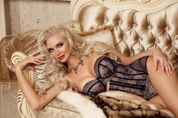 fashion interior photo of gorgeous sexy blond girl in lingerie corset lying on luxury modern sofa in golden bedroom. beauty glamour style portrait. - burlesque stock photos and pictures