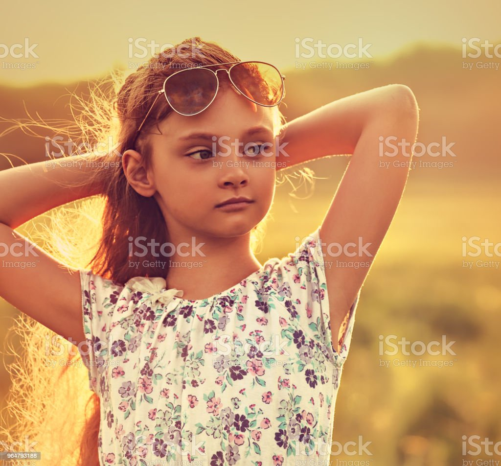 Fashion kid girl relaxing in fashion sunglasses on spring nature orange bright background. Soft light. Closeup toned color portrait royalty-free stock photo