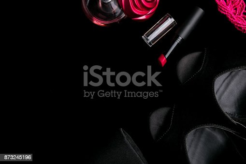 istock Fashion Lady Accessories Set. Black and pink. Minimal. Shoes, bracelet, perfume, lipstick and bag on black background. Flat lay. 873245196