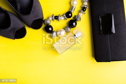 istock Fashion Lady Accessories Set. Black and yellow. Minimal. Black Shoes, bracelet, perfume and bag on yellow background. Flat lay. 873278826