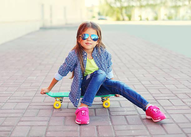 mode kleines mädchen kind sitzt auf skateboard auf die stadt - sommer teenagermode stock-fotos und bilder
