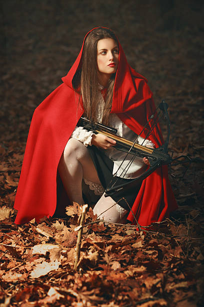 fashion little red riding hood posing in the forest - crossbow stock pictures, royalty-free photos & images