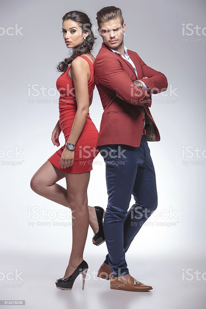 fashion man and woman standing back to back stock photo