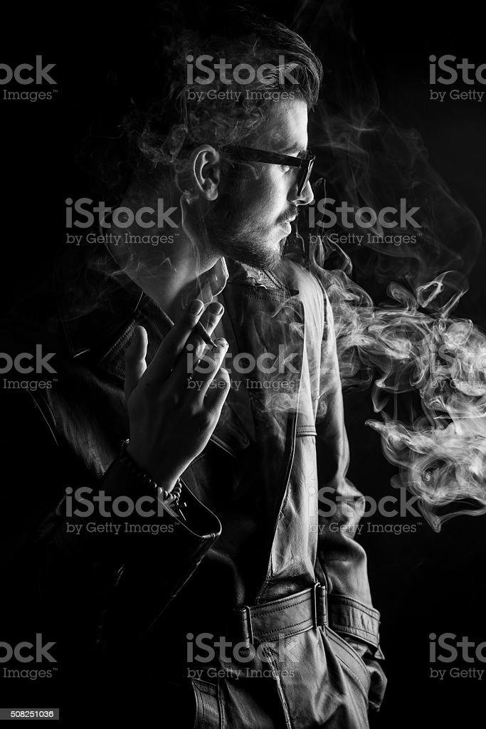 Fashion man enjoying his cigarette stock photo