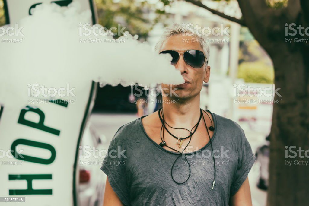 Fashion Man in a sunglasses smoking Vape with big clouds of vapor, outdoor street vaping or quitting smoking stock photo