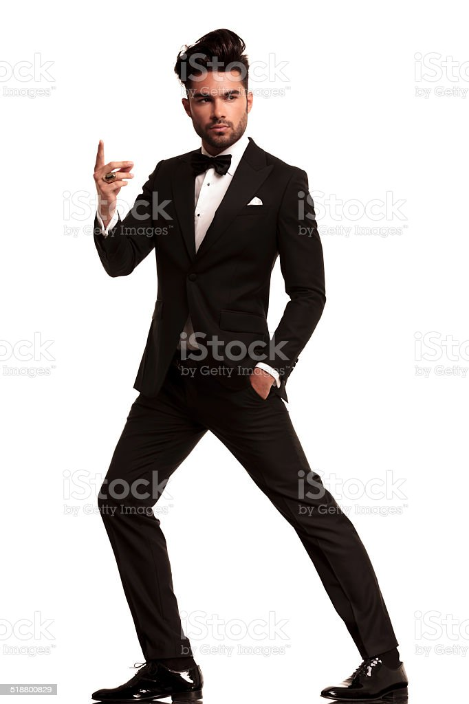 fashion man in tuxedo snapping his finger stock photo