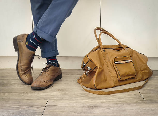 Fashion man legs in indigo navy blue pants Fashion man legs in indigo navy blue pants, navy anchor socks, leather shoes and leather tote bag ( Vintage tone color ) anchor athlete stock pictures, royalty-free photos & images