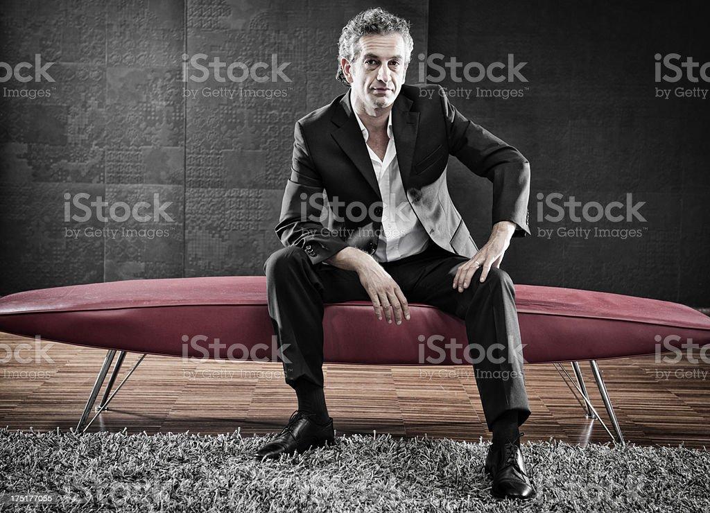 Mode Mann schaut die Kamera und posieren auf dem sofa Lizenzfreies stock-foto