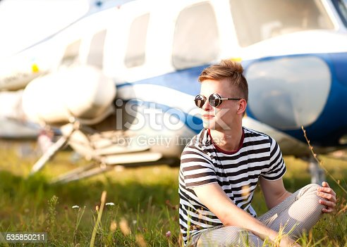 istock fashion man near helicopters at the airport 535850211
