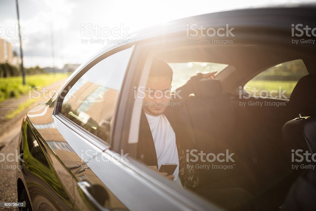fashion man on the phone inside a car