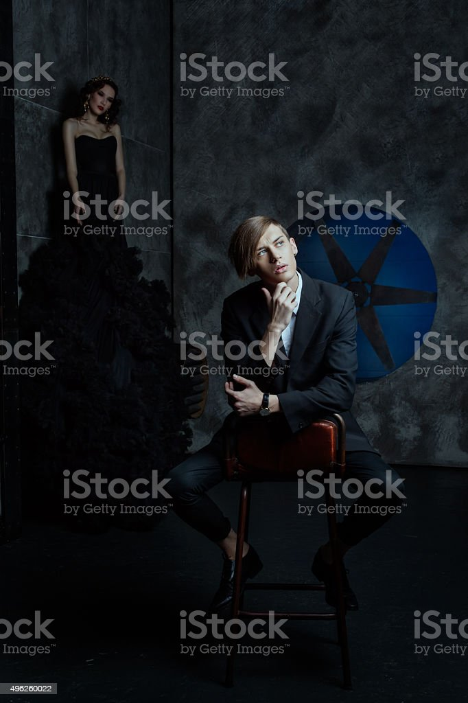 Fashion man sitting on a chair in  room and dreaming. stock photo