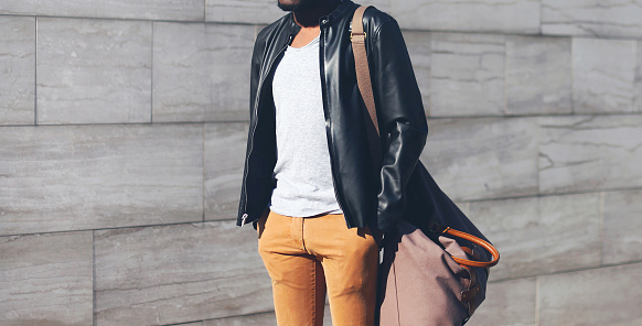 627398448 istock photo Fashion man wearing a black biker leather jacket with bag in evening city on a gray background 905885012