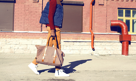 627398448 istock photo Fashion man wearing a vest jacket holds bag is walking in the city 877382872