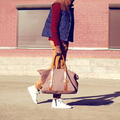 627398448 istock photo Fashion man wearing a vest jacket with bag is walking in the city 877382998