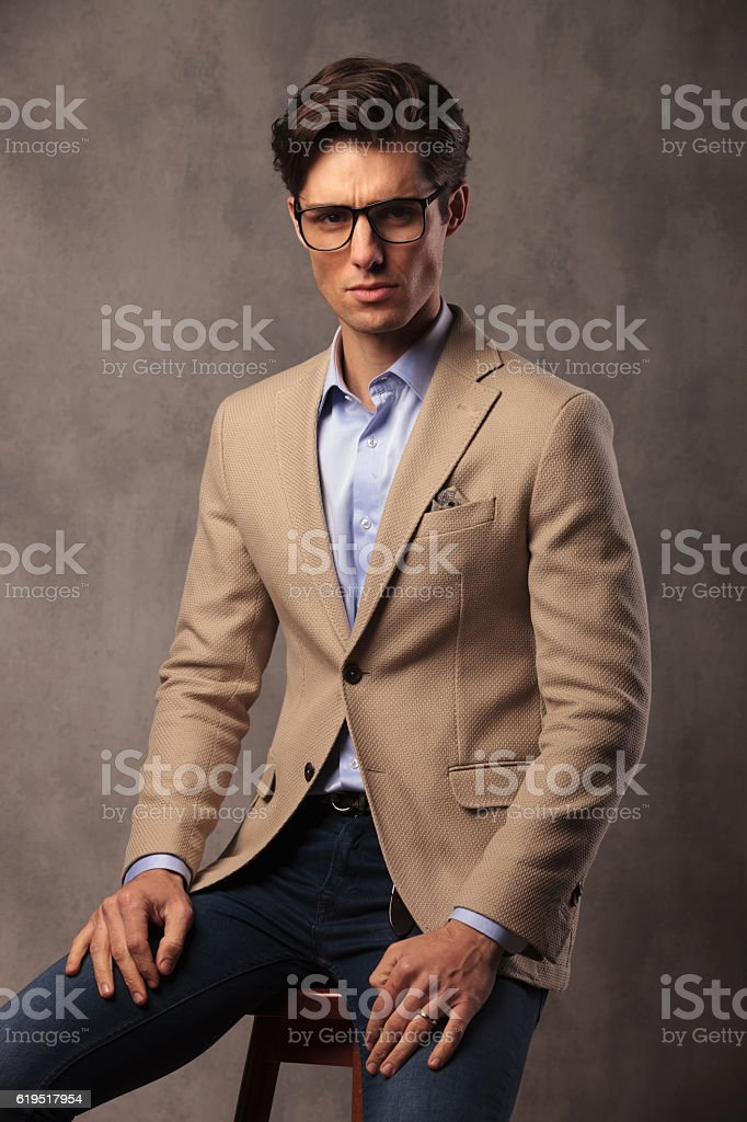 fashion man wearing glasses and sitting – zdjęcie