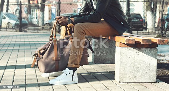 istock Fashion man with bag sits on a bench in the city close-up 867585926
