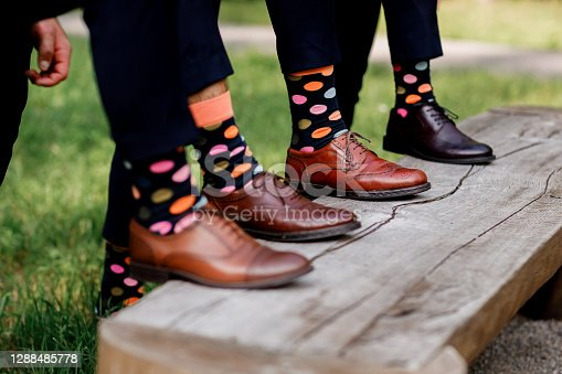 Fashion men footwear. guys wearing leather shoes and colorful socks on wooden bench. selective focus