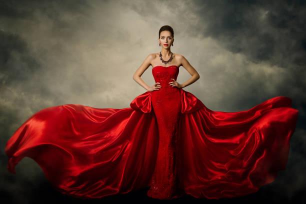 modell art kleid mode, elegante frau in roten retro-kleid, seidenstoff flattert im sturm - lange abendkleider stock-fotos und bilder