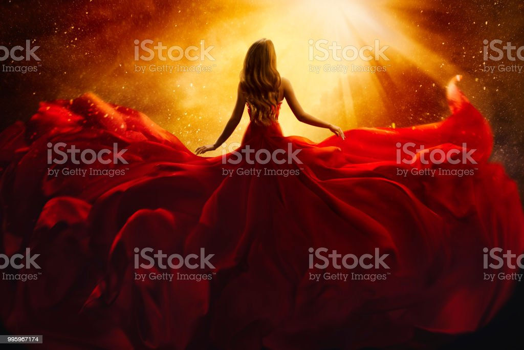 Fashion Model Back Side in Red Flying Dress, Woman Rear View, Gown Fabric Fly on Wind, Beautiful Girl Looking to Light stock photo