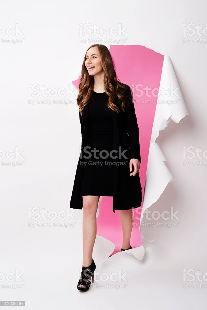 Fashion model emerging from torn paper in studio stock photo
