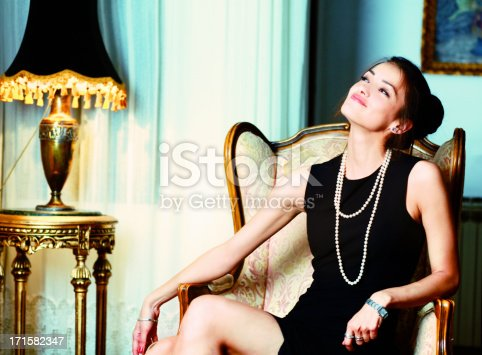 Fashionable brunette relaxing in the sofa chair, smiling with satisfaction.