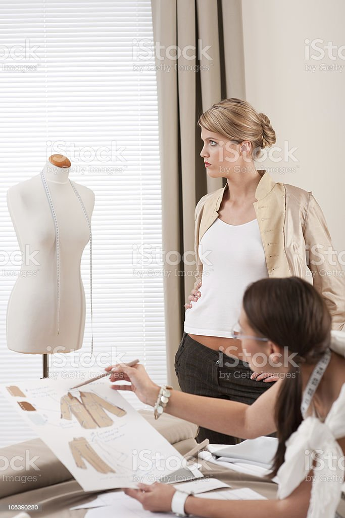 Fashion model fitting clothes by professional designer woman royalty-free stock photo