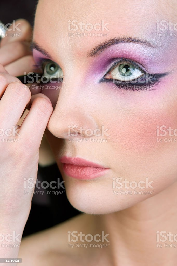 Fashion model getting an unusual make up royalty-free stock photo