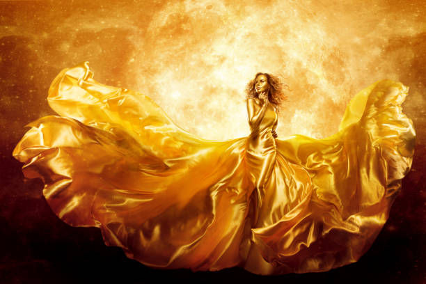 Fashion Model Gold Color Skin, Fantasy Woman Beauty in Artistic Waving Dress, Flying Silk Gown stock photo