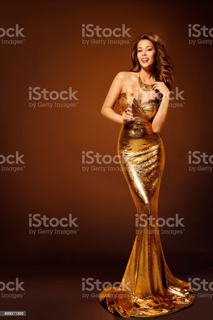 Fashion Model Gold Dress, Woman in Beauty Golden Gown with Champagne, Lady in Long Clothes stock photo