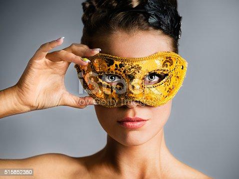 Close-up portrait of attractive fashion model hiding face behind golden mask. Studio shot.