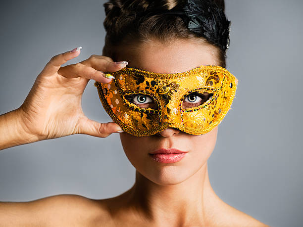 fashion model hiding face behind golden mask - mask disguise stock photos and pictures
