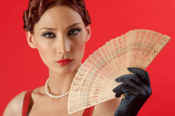 Fashion model holding fan dressed retro style red bustier stock photo