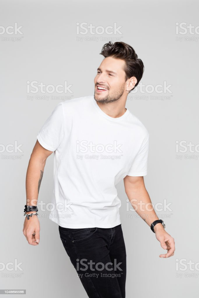 Fashion model in casuals smiling Portrait of fashion model in casuals smiling on grey background 25-29 Years Stock Photo