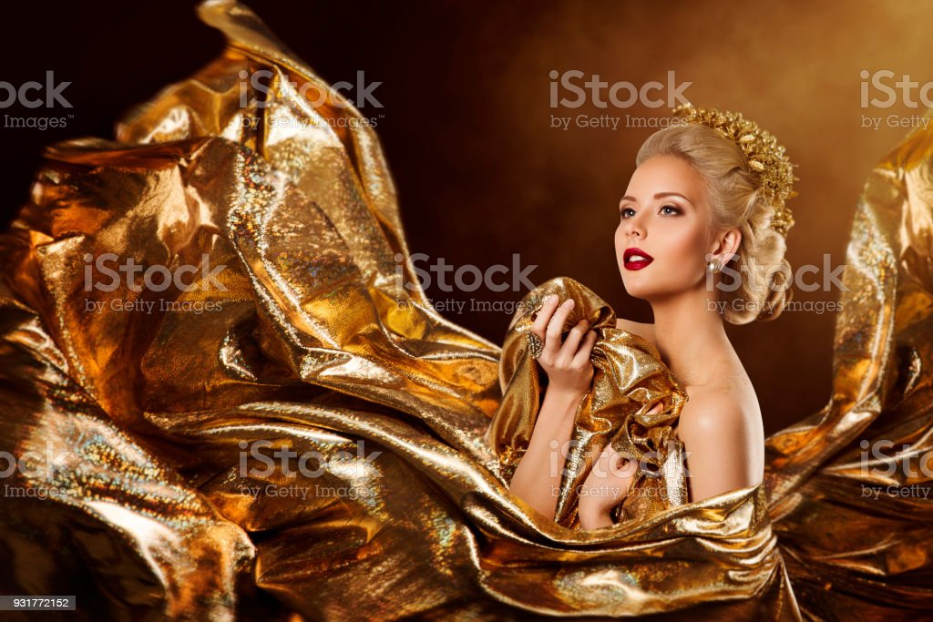 Fashion Model in Flying Gold Dress, Woman Beauty Portrait, Waving Golden Sparkling Fly Fabric stock photo