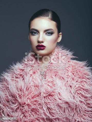Young fashionable woman wearing pink faux fur coat. Professional make-up and hairstyle. High-end retouch.